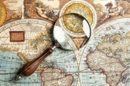 21145611-Magnifying-glass-and-ancient-old-map-Stock-Photo-world